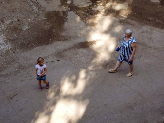 Заботливая бабушка выгуливает внучку на поводке, чтоб не убежала